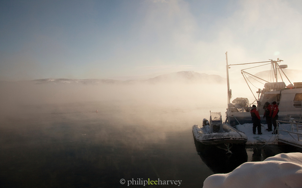 An inflatable Zodiac craft, sits frozen over a misty lake at Jarfjord near Kirkeness, Finnmark region, northern Norway