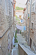 A steep and narrow street between old houses with lots of clothes lines with washing hanging to dry Dubrovnik, old city. Dalmatian Coast, Croatia, Europe.