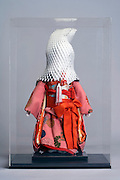 Japanese doll with improvised protective wrapping over its head and plexiglas cover case