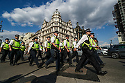 Police officers wearing face masks march by Parliament Square during an Extinction Rebellion climate change protest in London, Tuesday, Sept 1, 2020. (VXP Photo/ Vudi Xhymshiti)