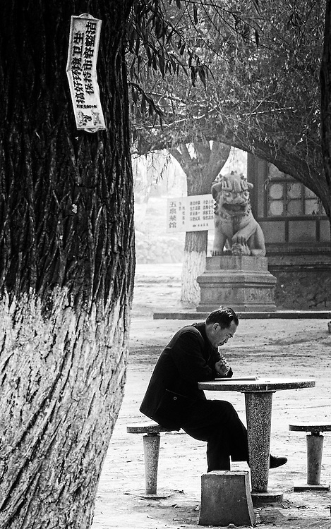 Poet at dawn before the main gate of a temple, China.