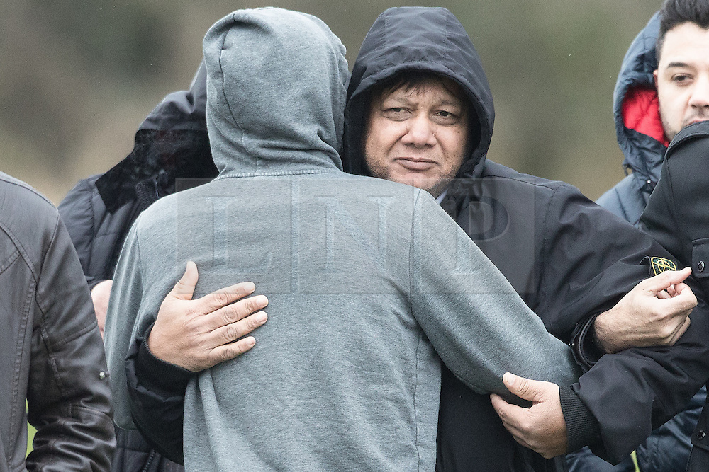 © Licensed to London News Pictures. 06/01/2017. Huddersfield, UK. Mohammed Yaqub (C), father of Yasser Yaqub hugs a mourner at the funeral of Yassar Yaqub at Hey Lane Cemmetary in Huddersfield, West Yorkshire. Yaqub, 28, from Huddersfield, was shot dead in a car stopped near junction 24 of the M62 as part of a planned police operation. Photo credit: Joel Goodman/LNP