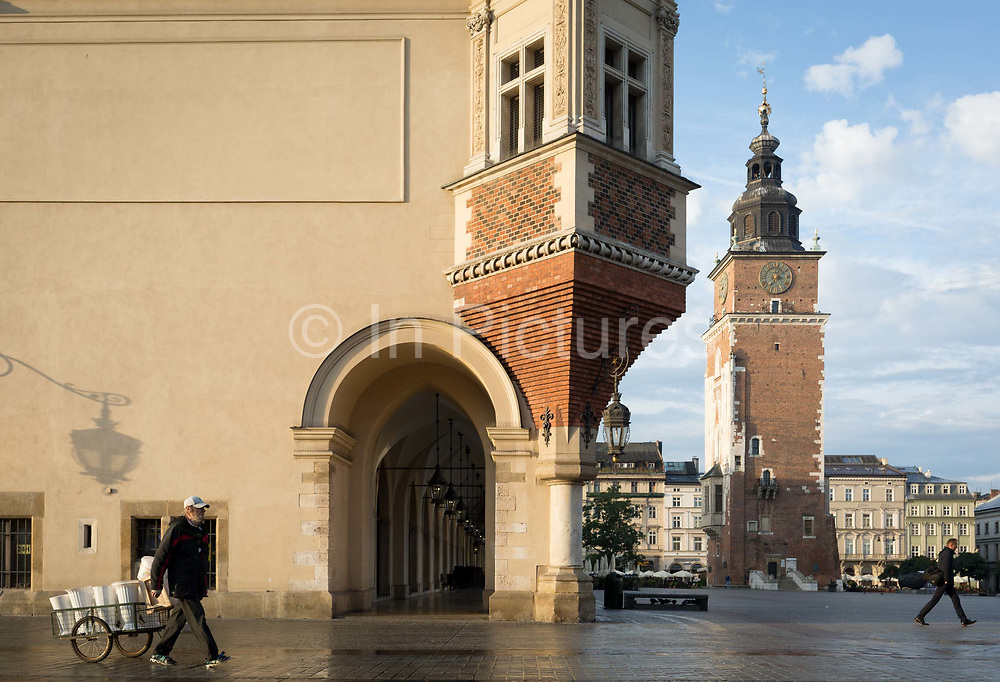 A flower seller pulls his cart to refill fresh water from a nearby tap and past the architecture of the Cloth Hall and the the City Hall Tower right on Rynek Glowny market square, on 23rd September 2019, in Krakow, Malopolska, Poland.