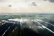 Nederland, Overijssel, Gemeente Steenwijkerland, 10-10-2014; Nationaal Park De Weerribben, het landschap is het resultaat van het winnen van turf waardoor 'trekgaten' ontstonden. De legakkers ('ribben') werden gebruikt voor het drogen van de turf. Tegenwoordig vindt er rietteelt plaats (dekriet). De rook is het gevolg van het branden van rietvelden en wordt toegepast om het riet wat door intensief maaien verruigd is en door ziekte is aangetast, weer nieuw leven in te blazen. <br /> The National Park Weerribben. The landscape is the result of the extraction of peat, after digging the peat (creating the 'pull holes'), it was to layed to dry on fields (the 'ribs'). Today production of reed takes place (thatching), the smoke was caused by burning cane fields The controlled burning of the reed fields to renew the reed.<br /> luchtfoto (toeslag op standard tarieven);<br /> aerial photo (additional fee required);<br /> copyright foto/photo Siebe Swart