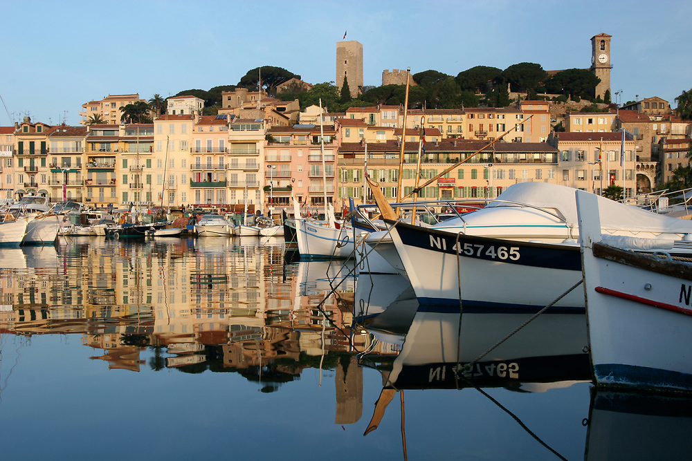 Cannes Port with fishing boats and view of Le Suquet Hill, Cannes France