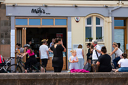 Portobello, Scotland, UK. 24 June, 2020. With sunshine and temperatures of 24C , the beach and promenade at Portobello outside Edinburgh were busy with the public who were enjoying the freedom of a relaxation of the covid-19 lockdown. Miro's cafe was doing a brisk trade. Iain Masterton/Alamy Live News