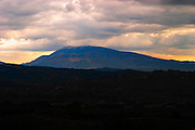 The Mont Ventoux from the north from a distance the top covered in snow. Dark silhouette at sunset.  Vaucluse, France, Europe