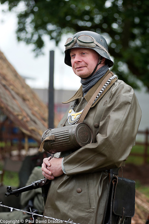 Known by German soldiers of the period as kettenhund or Chain Dogs a reenactor portrays a second world war Field Policeman at the Northallerton Wartime Weekend. He is wearing the classic German Steel Helmet (Stahlhelm) around his neck is a Gasmask canister and his goget. The coat is a waterproof Motorcyclist coat made from rubberised fabric known as a kradmantel <br /> 18th and 19th June  2011<br /> Images © Paul David Drabble