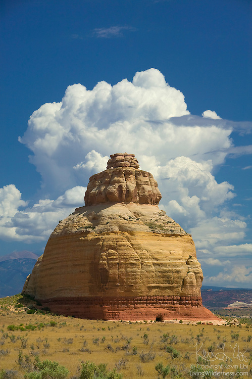 Billowing cumulus clouds tower over the summit of Church Rock, a sandstone monolith found along the Indian Creek Corridor Scenic Byway near Monticello in Eastern Utah.