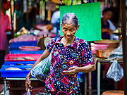 20 JUNE 2018 - BANGKOK, THAILAND: A shopper with a plastic bag of purchases on her shoulder counts her change at Makkasan Market, a small local market in central Bangkok. Officials in Thailand are wrestling with Thais use of plastic bags. The issue became a public one in early June when a whale in Thai waters died after ingesting 18 pounds of plastic. In a recent report, Ocean Conservancy claimed that Thailand, China, Indonesia, the Philippines, and Vietnam were responsible for as much as 60 percent of the plastic waste in the world's oceans.     PHOTO BY JACK KURTZ