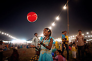 A girl is playing with a red ball during celebrations for the Dussehra Festival in Bhopal, Madhya Pradesh, India, site of the 1984 Union Carbide (now DOW Chemical) gas disaster.