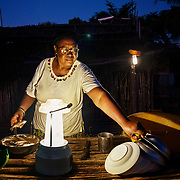 """Yollande Randrianambinina cooks in front of a solar lamp. Dubbed the """"Solar Mamas,"""" Randrianambinina and her friends were the first in their village to join a program by the World Wildlife Fund (WWF) to become electric engineers capable of installing and repairing solar panels. <br /> Across much of this African nation, where 77% of the population of 21 million has no access to electricity -- a figure rising to a staggering 94% among the rural population  -- nighttime means the burning of kerosene lamps and diesel engines, which fill the houses with toxic smoke. And it means the destruction of forests for firewood in one of the world's most biologically-diverse habitats. <br /> <br /> Darkness also brings the threat of crime, violence and accidents.<br /> <br /> Madagascar is the world's forth largest island off the coast of east Africa."""