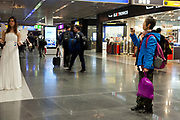 woman photographing shopping arcade entertainment with an smartphone at Frankfurt airport during the Christmas season