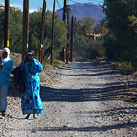 Africa, Morocco, Skoura. Moroccan women in blue walking on road.