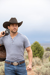 hot rugged cowboy holding a saddle on a ranch