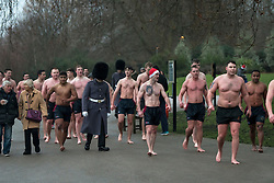 © Licensed to London News Pictures. 25/12/2017. London, UK. Members of The Scots Guards leave the Serpentine after braving the cold waters at the Serpentine Lake in Hyde Park, London on Christmas Day, December 25, 2017. Photo credit: Ben Cawthra/LNP