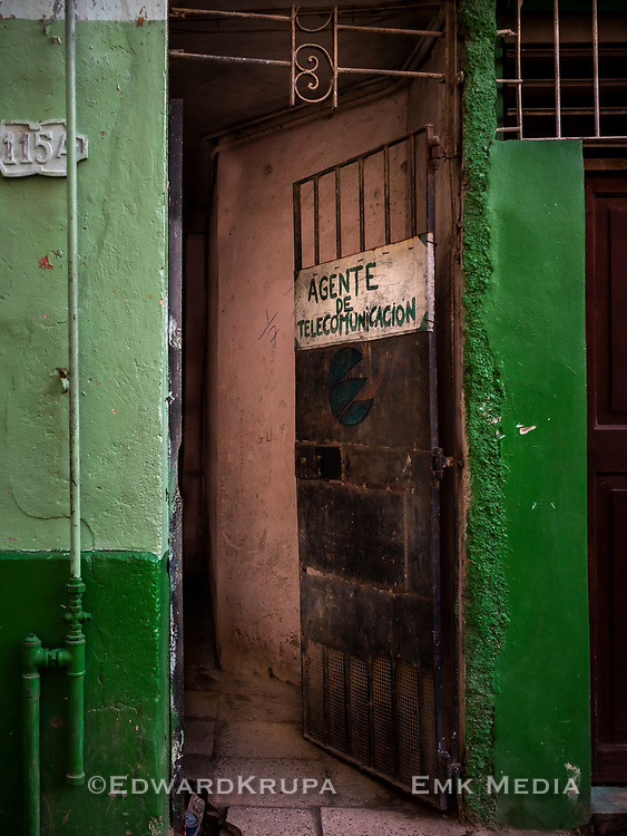 A door with a hand painted sign AGENTE DE TELECOMUNICACION in Havana.
