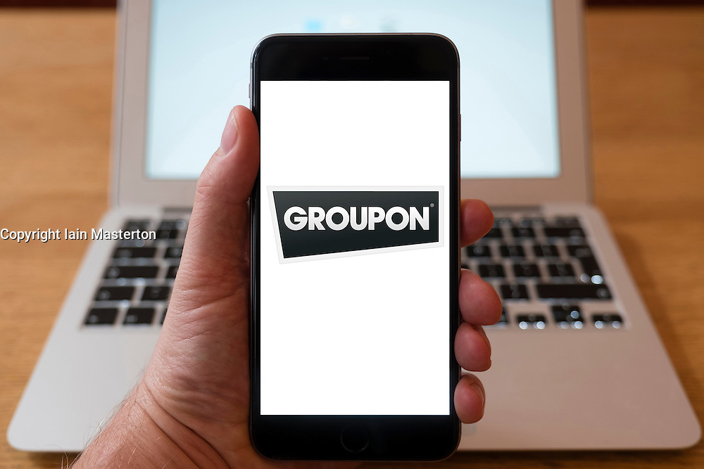 Using iPhone smartphone to display logo of Groupon worldwide e-commerce marketplace app