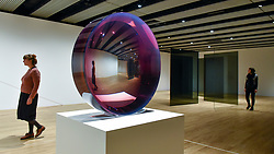 """© Licensed to London News Pictures. 25/09/2018. LONDON, UK. Gallery staff members walk by (L to R) """"Untitled (Parabolic Lens)"""", 1971, by Fred Eversley and """"Standing Walls"""", 1969/2016 by Larry Bell. Preview of """"Space Shifters"""" at the Hayward Gallery, an exhibition which features artworks by 20 leading international artists that disrupt the visitor's sense of space and alter their perception of their surroundings.  The show runs 26 September to 6 January 2019.  Photo credit: Stephen Chung/LNP"""