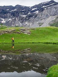Woman hiking in the High Pyrenees walking on shore of small lake, France