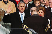 President of the United States, George W. Bush, takes the oath of office from Chief Justice William Rehnquist (back to camera) as First Lady Laura Bush observes during the 55th presidential inauguration ceremony on the steps of the capitol in Washington, D.C., Friday, January 20, 2005.