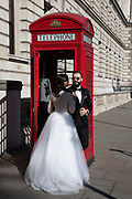 Couple have some wedding photographs taken beside one of the iconic red telephone boxes in London, United Kingdom. This icon of design is now just an object as telecomunication via mobile phone has made the public call box all but obsolete.