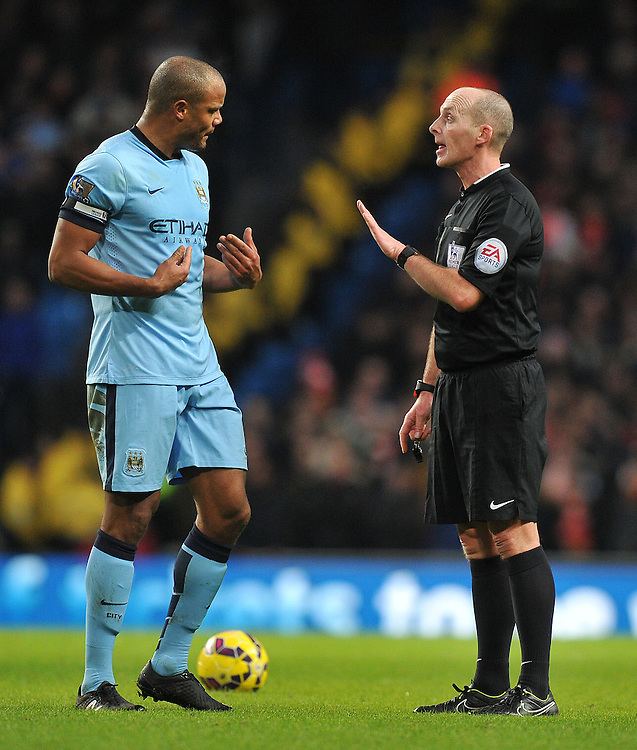 Do you mean me? asks Manchester City's Vincent Kompany of referee Mike Dean<br /> <br /> Photographer Dave Howarth/CameraSport<br /> <br /> Football - Barclays Premiership - Manchester City v Arsenal - Sunday 18th January 2015 - Etihad stadium - Manchester<br /> <br /> © CameraSport - 43 Linden Ave. Countesthorpe. Leicester. England. LE8 5PG - Tel: +44 (0) 116 277 4147 - admin@camerasport.com - www.camerasport.com