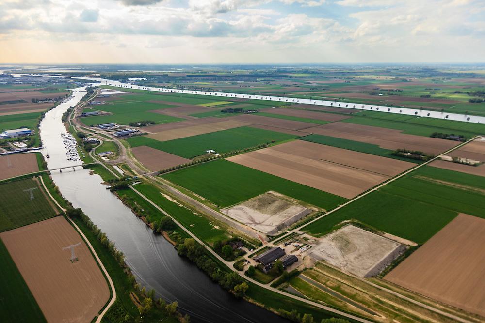 Nederland, Brabant, Gemeente Waspik, 09-05-2013; Overdiepsche polder: in het kader van het programma 'Ruimte voor de Rivier' (bescherming tegen hoogwater door rivierverruiming), zal de dijk langs de Bergsche Maas (rechts in beeld) verlaagd worden. Bij hoogwater kan de Overdiepse polder overstromen. De boerderijen in de polder worden gesloopt en verplaatst naar de dijk van het Oude Maasje. De nieuwe boerderijen met bijgebouwen komen op terpen.<br /> Depoldering of Overdiep Polder, farms are relocated and built on mounds. This makes it possible for the river to overflow the polder in case of heigh waters.<br /> luchtfoto (toeslag op standard tarieven);<br /> aerial photo (additional fee required);<br /> copyright foto/photo Siebe Swart.