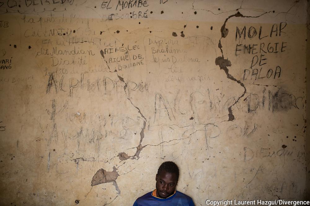 30012018. Niger. Agadez. Ghetto en bordure de la ville où se cachent les migrants de passage dans leur route vers l'Algérie et la Libye avec en ligne de mire l'Europe. Ils attendent ici le temps de trouver un passeur ou de récolter de l'argent pour poursuivre leur route en travaillant ou en faisant appel à leur famille. Mohamed (visage caché), ivoirien, 19 ans, est ici depuis 9 mois et gère le ghetto pour le propriétaire. Mohamed, 20 ans, burkinabé, Ibrahim, 15 ans, malien etIbrahim, 17 ans, malien aussi vivent dans le ghetto en attendant un départ vers la Libye ou pour rentrer chez eux.