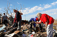 Sandra Booth-Knight throws a dish into the trash at her tornado-destroyed home across the street from the Plaza Towers elementary school in Moore, Oklahoma May 22, 2013. A massive tornado tore through a suburb of Oklahoma City, wiping out whole blocks and killing at least 24.   REUTERS/Rick Wilking (UNITED STATES)