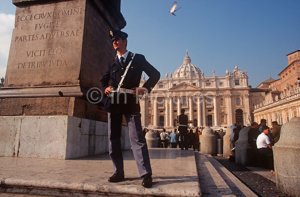Two police officers keep watch over tourists in the centre of St. Peters Square in the Vatican, on 3rd November 1999, in Rome Italy.