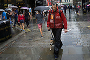 London, UK. Sunday 23rd August 2015. Heavy summer rain showers in the West End. People brave the wet weather armed with umbrellas and waterproof clothing. Big Issue seller and his dog in Covent Garden.