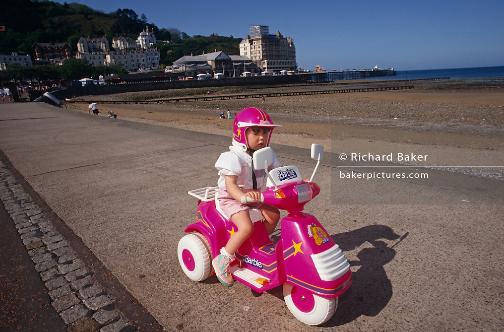 On a bright summer afternoon, a young spoiled girl shows-off by riding her favourite motorized Barbie trike along The Parade, the main promenade in the north Welsh seaside town of Llandudno, Wales. Wearing a bright pink helmet and travelling on the matching pink toy bike, she trundles along with the low-tide coast over her left shoulder. Barbie is a best-selling fashion doll launched in 1959 and produced by Mattel, Inc. The brand's merchandising reaches far and wide to countries and cultures around the world and this little girl seems to be the happiest on the beach, enjoying a generous present perhaps from a parent. She is the exact age that Mattel are targeting when they market these toys to accompany their dolls and accessories though the industry has come under fire for its controversial stereotyping of gender and subtle sexuality.