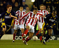 Photo: Richard Lane.<br /> Wimbledon v Stoke City. FA Cup 5th Round. 03/01/2004.<br /> Darel Russell breaks away from Dean Lewington and Nigel Reo-Coker.