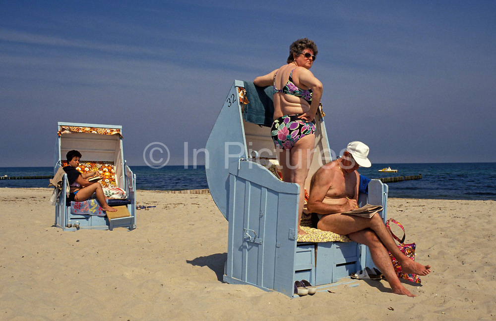 A year after the fall of the Berlin Wall and the end of the Communist Eastern Bloc, sunbathing Germans face away from the wind on the beach at the Baltic coast, a region of East Germany, 1st June 1990, Bezirk Rostock, eastern Germany former DDR. The Bezirk Rostock, the northernmost part of the DDR, was on the coast of the Baltic Sea, in front of the Danish coasts. It bordered with the Bezirke of Schwerin and Neubrandenburg, with Poland and West Germany.