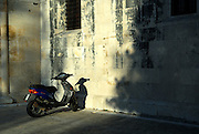 Scooter parked against ancient stone wall, late afternoon sunlight. Trogir, Croatia
