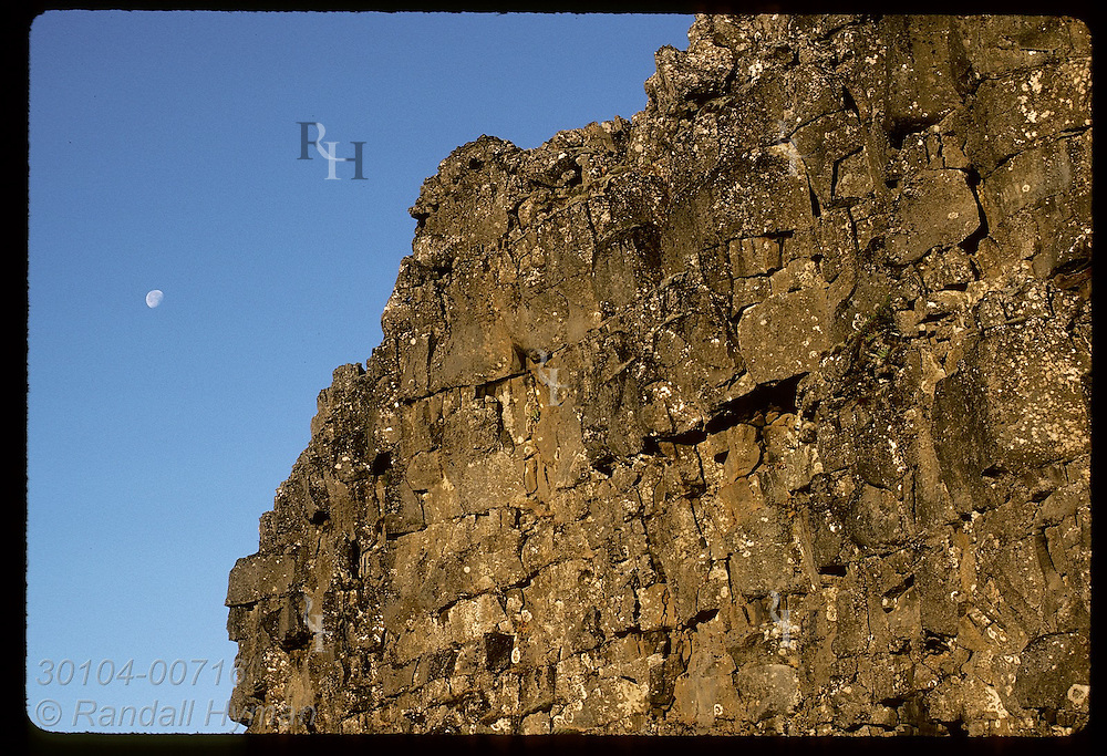 Moon hangs over rock wall, Logberg, used by Vikings to cast voice to parliament crowd; Thingvellir Iceland