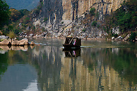Access to the ancient Huashan rock paintings is via the Ming River, in Guangxi province.   Surrounded by mountainous limestone karsts is a boat making its way downriver.