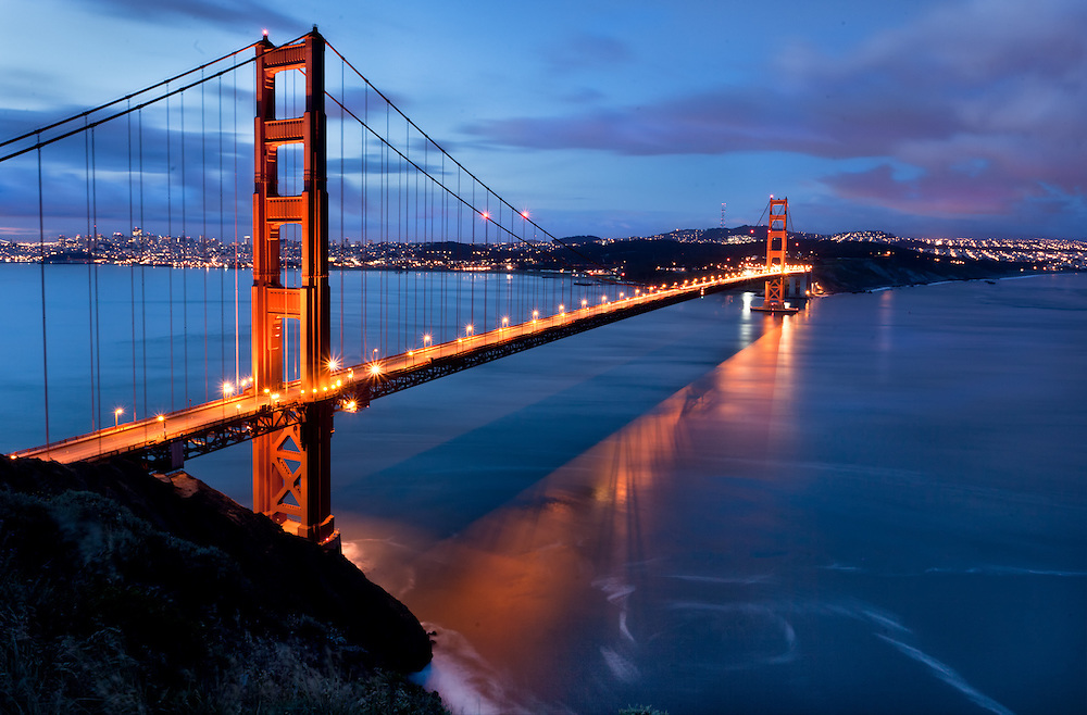 World famous San Francisco California landmark, the Golden Gate Bridge taken at sunrise as a storm approaches the bay area. This is a super long exposure taken a half hour before sunrise in the Marin headlands above Fort Baker.