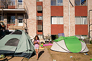 18 AUGUST 2020 - CEDAR RAPIDS, IOWA: A girl walks between the tents in front of Cedar Terrace Apartments in Cedar Rapids. Most of the tenants in the complex are refugees from Africa and Micronesia who have chosen the camp in front of the buildings rather than move to shelters because they're worried about looters taking their belongings. Cedar Rapids was the state's hardest hit city by the derecho that roared across Iowa last week. City officials said the damage left by the derecho was more extensive than the 2008 flood that destroyed much of its downtown. City residents are reporting that almost every home was damaged in the storm, many businesses were closed, and up to half of the city's tree canopy was destroyed. A week after the storm, more than 40,000 homes were still without power. A spokesman for Alliant Energy said the utility has replaced as many power poles in one week that they normally replace in 8 months. On Monday, President Trump approved a $4 billion emergency declaration for Iowa to aid in derecho recovery.   PHOTO BY JACK KURTZ