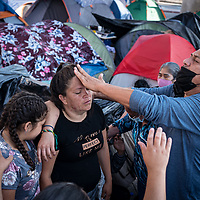 An evangelical church group from San Diego, USA, visits the El Chaparral camp of asylum seekers in Tijuana, Mexico. While church members lays out a table of food brought by the group, and a queue of hungry migrants forms behind it, a male pastor shouts prayers excitedly into a loudspeaker and another lays his hands on women 'to heal them'. Once lengthy prayers are said, food is served. Church groups come to the camp every day, some require a lot of attention and participation from the migrants than others before they serve them food, others quickly bless the food and distribute it. For some the long services are a welcome distraction, and they provide spiritual sustenance in a desperate situation.