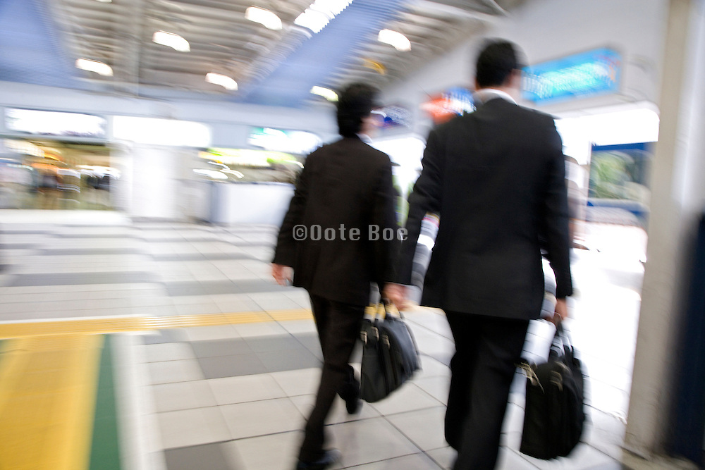 two businessmen hurrying on their way to work