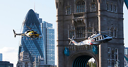 © London News Pictures. 09/06/2012. London, UK. Two helicopters performing stunts during filming at Tower Bridge in London on June 9, 2012.  Both helicopters flew through the gap between the upper walkway and the road of the bridge during the filming, with one of the helicopters painted in the colours of the Union Flag. The Port of London Authority said the helicopters were filming footage for the upcoming Olympic Games. Photo credit: Vickie Flores/LNP
