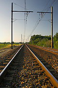 Train track and overhead cables  at  level crossing near Barsac station, Bordeaux  region, France.
