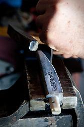 """Avigliano (PZ), 04-10-2010 ITALY - Vito Aquila, artigiano di Balestre. Il coltello di Avigliano, comunemente conosciuto come """"balestra"""", impreziosito con decorazioni in argento e ottone che le conferivano un certo valore non solo artistico,ha identificato per tutto l'Ottocento e parte del Novecento il carattere fiero e risoluto del popolo aviglianese, come attestato in una lunga casistica di riscontri documentari. La """"balestra"""" è un'arma a tutti gli effetti, ed è già considerata -nell'ambito delle manifatture di ferro - oggetto di pregio. Per l'approvvigionamento dell'argento e dell'ottone destinati alla decorazione del manico del coltello gli armieri si rivolgevano agli orefici o agli ottonari. La """"balestra"""" era un'arma del popolo, pronta ad essere impiegata, a seconda delle circostanze, per la difesa o l'offesa tanto dagli uomini quanto dalle donne. Queste, la ricevevano come regalo di fidanzamento dal rispettivo promesso sposo per meglio difendere il proprio onore, perpetrando un'usanza molto sentita almeno fino ai primi decenni del '900..Nella Foto: Disegno ed intaglio del manico."""