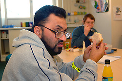 Man with learning disabilities eating lunch in community centre; Bradford Yorkshire UK
