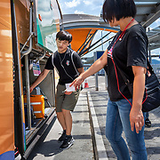Passengers board a bus at the Hong Kong–Zhuhai–Macau Bridge (HZMB), officially the Hong Kong–Zhuhai–Macao Bridge, is a 55-kilometre (34 mi) bridge–tunnel system consisting of a series of three cable-stayed bridges, an undersea tunnel, and four artificial islands. It is both the longest sea crossing and the longest open-sea fixed link on earth.It was opened in October 2018.