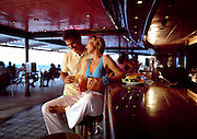 A young couple dressed for the summer hangs out in a bar inside of a Cruise ship at sea