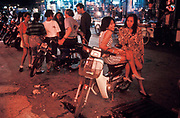 Young prostitutes await business whilst others talk to foreign tourists in the notorious sex industry city of Pattaya, Thailand.