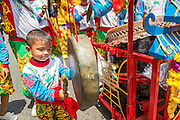 """05 JULY 2014 - BANGKOK, THAILAND:  A boy plays a cymbal in Bangkok during a parade for vassa. Vassa, called """"phansa"""" in Thai, marks the beginning of the three months long Buddhist rains retreat when monks and novices stay in the temple for periods of intense meditation. Vassa officially starts July 11 but temples across Bangkok are holding events to mark the holiday all week.   PHOTO BY JACK KURTZ"""